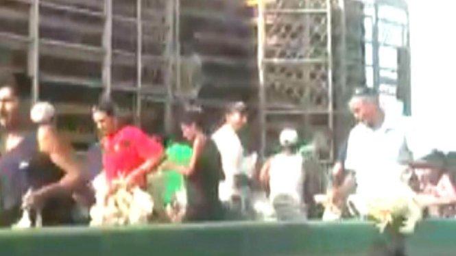 Hình cảnh cắt ra từ đoạn video cho thấy người dân đổ xô vào chiếc xe tải bị chặn lại để bắt gà - Ảnh: T13