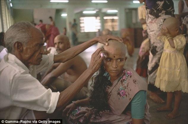 Một người phụ nữ đang được cạo đầu tại Ấn Độ.
