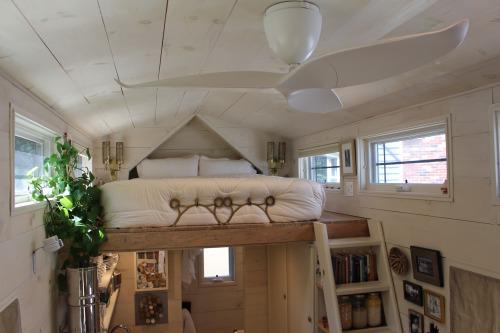 Bên trên khu vực nhà bếp là một gác xép nhỏ với giường ngủ tràn ngập ánh sáng và cây xanh.
