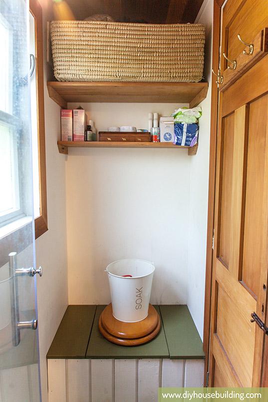 Không gian trong nhà vệ sinh được bố trí gọn gàng bằng việc tận dụng những kệ để đồ và móc treo sau cánh cửa.
