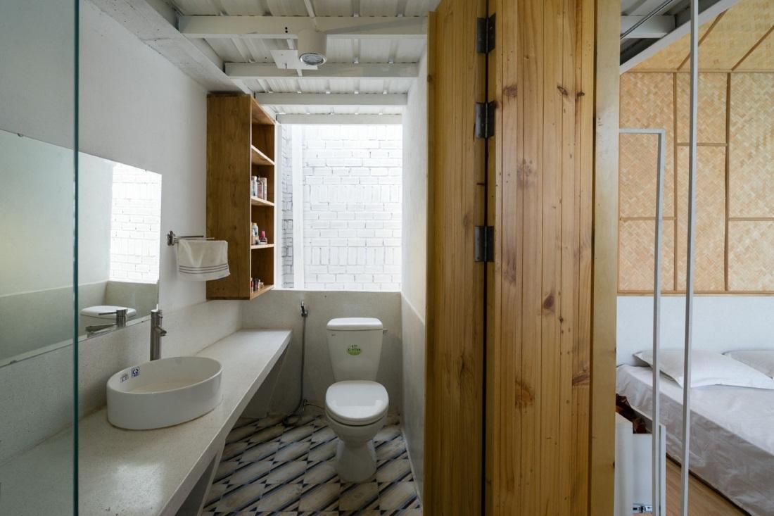 Phòng vệ sinh chung thoáng rộng với tủ gỗ đựng đồ nhà tắm tiện dụng.