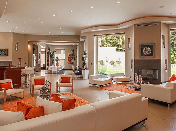 Phòng khách sử dụng màu sắc trung tính, các khu vực được phân chia tinh tế bằng những tấm thảm màu cam nổi bật.