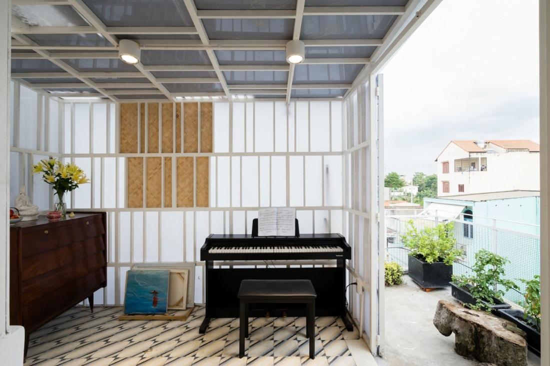 Phía bên ngoài còn có một không gian thoáng mát với cây xanh và một chiếc đàn piano xinh xắn.