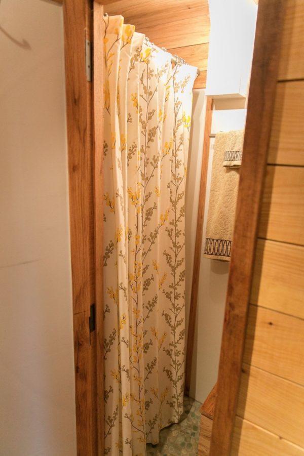 Khu vệ sinh nhỏ với rèm che được bố trí cuối nhà.