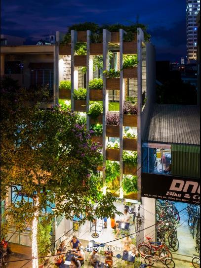 Ngôi nhà nổi bật giữa khu phố trong ánh sáng đèn điện khi về đêm.