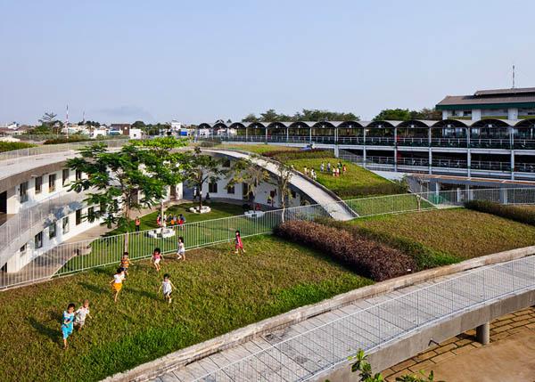 Công trình có thiết kế hình xuyến kết nối mái nhà với sân chơi tạo nên một màu xanh trải dài bất tận.