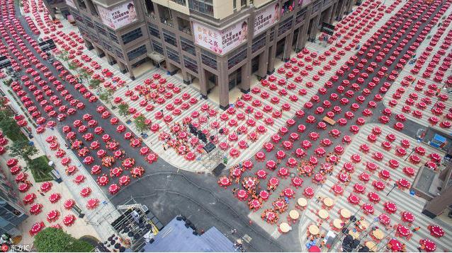 Những dãy bàn ăn với ghế đỏ, khăn trải bàn đỏ được sắp xếp ngay ngắn, thẳng hàng dọc các con đường.