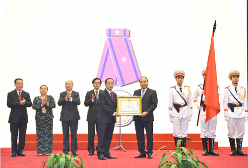 Thay mặt lãnh đạo Đảng, Nhà nước, Thủ tướng Nguyễn Xuân Phúc trao Huân chương Lao động hạng Ba cho Hiệp hội DNNVV. Ảnh: VGP/Quang Hiếu