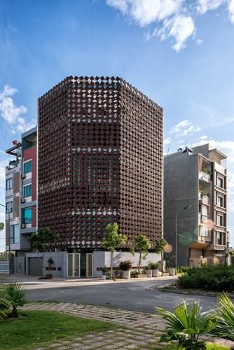 Thay vì bức tường bao vây và những cửa sổ, ngôi nhà này được thiết kế 2 lớp với mặt trong là lớp kính và mặt ngoài là những viên gạch gốm tái chế.