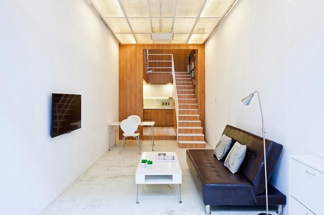 Không gian phòng khách được bố trí đơn giản với ghế sofa dài cùng bàn trà có chân giúp không gian trở nên thoáng đãng hơn. Chiếc ti vi được gắn cố định vào tường để tiết kiệm tối đa diện tích.