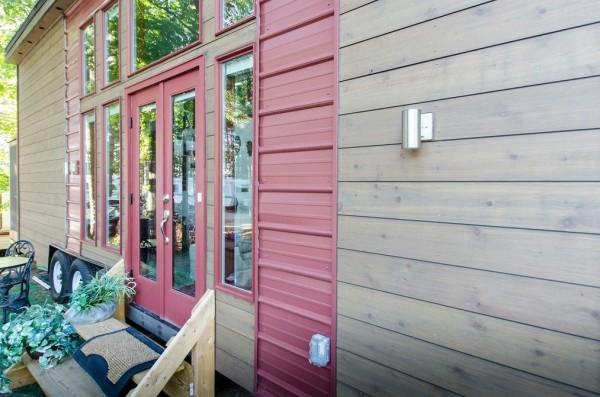 Lối vào nhà bắt mắt với màu sơn đỏ và những cửa kính trong suốt.