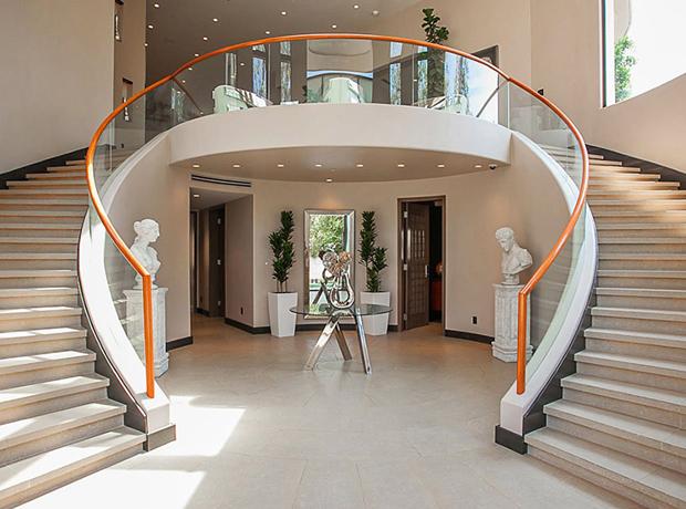 Cầu thang uốn cong thanh lịch chia thành hai bên và dẫn lên tầng trên, các ô cửa được mở rộng để đón nhận nguồn sáng tự nhiên.