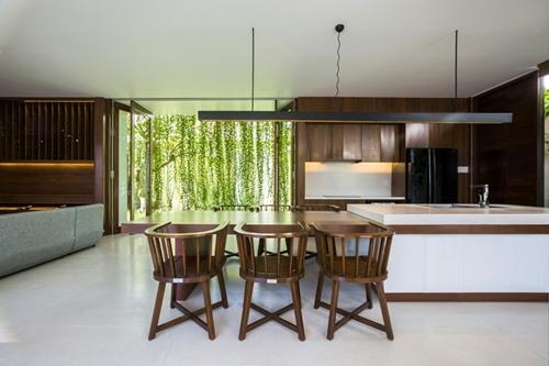 Khu bếp ăn đặt cạnh phòng khách rộng rãi với phần nội thất được làm từ gỗ.