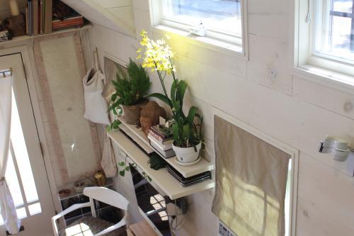 Ngay lối vào nhà là phòng khách được bố trí đơn giản với ghế sofa êm ái đặt dọc tường. Đối diện là chiếc ti vi được gắn chặt vào tường để tiết kiệm tối đa không gian. Bên trên là những kệ để đồ đẹp gọn được nhấn nhá bằng những chậu cây cảnh xinh xắn.