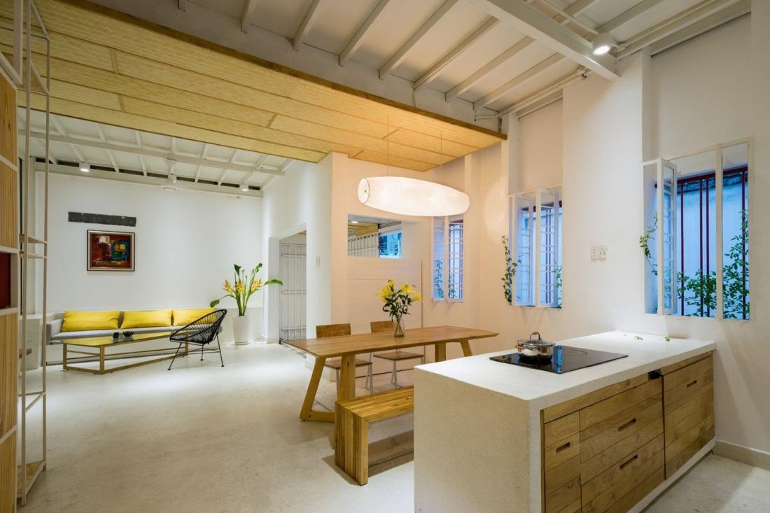 Khu bếp ăn tràn ngập ánh sáng với những chiếc cửa sổ kính. Không gian nơi bàn ăn còn được nhấn nhá bằng một lọ hoa xinh xắn đặt trên bàn cùng chiếc đèn điện vô cùng lạ mắt.