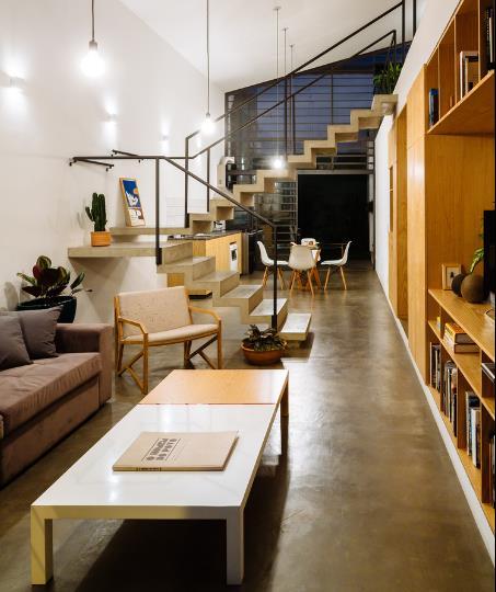 Khu vực phòng khách và bếp ăn tiện dụng được bố trí đơn giản và ngăn cách với nhau bằng một cầu thang gỗ đặt giữa nhà.