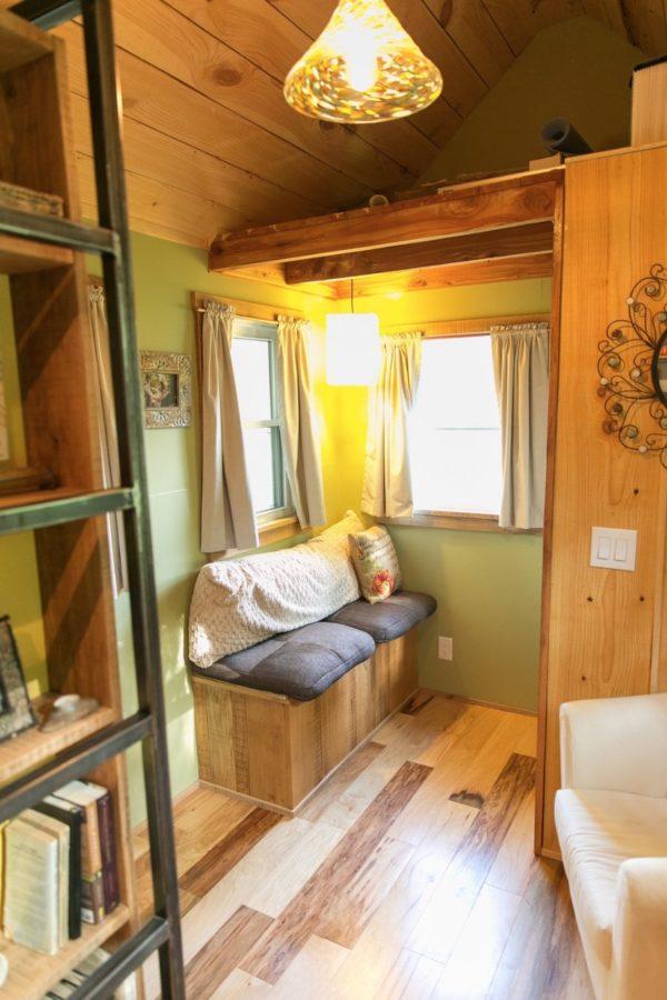 Không gian bên trong ngôi nhà tuy nhỏ nhưng thoáng sáng nhờ những cửa sổ kính. Ngay lối ra vào là khu vực tiếp khách được bố trí đơn giản với chiếc gối ôm họa tiết bắt mắt.