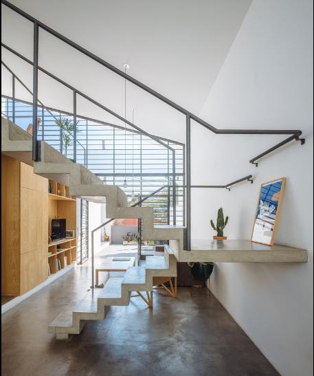 Toàn bộ nền nhà được làm bằng xi măng láng bóng vô cùng sạch sẽ và thoáng mát. Một hệ thống tủ kệ âm tường cũng được thiết kế chạy dọc bức tường khu vực tiếp khách.