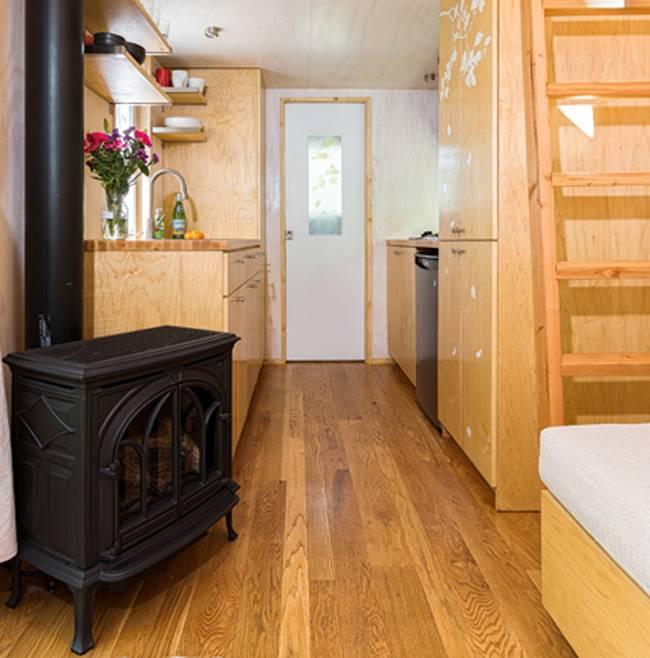 Đối diện phòng khách là khu vực bếp ăn và nhà tắm. Toàn bộ nội thất trong ngôi nhà nhỏ bé này từ bàn, ghế, hệ thống tủ kệ nơi bếp ăn…. đều được làm từ gỗ.