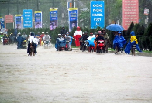 Người dân khó khăn di chuyển trên đường 2 Tháng 4 ngập nước