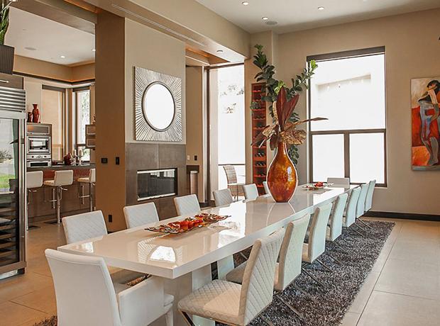 Một chiếc bàn màu trắng trải rộng theo không gian của phòng ăn. Chiếc lò sưởi hiện đại mang đến không khí ấm cúng cho những bữa tiệc đêm.