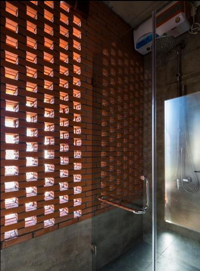 Khu vực nhà tắm thoáng sáng và thông gió nhờ bức tường gạch thông gió được khéo léo xếp tạo thành những ô thoáng.