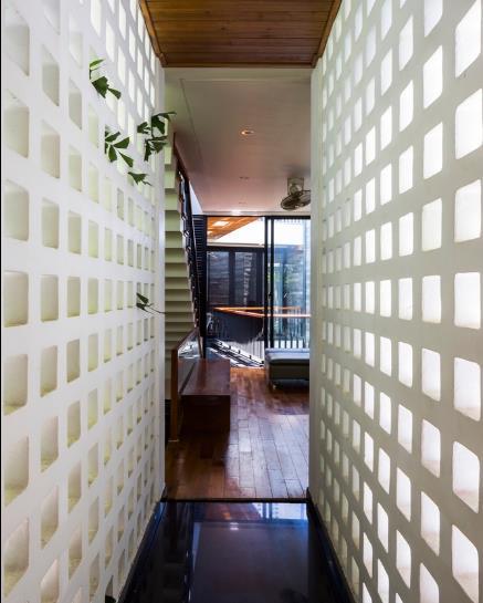 Giữa khu vườn là một hành lang nhỏ nối các phòng được xây cầu kỳ với những ô thoáng đẹp mắt.