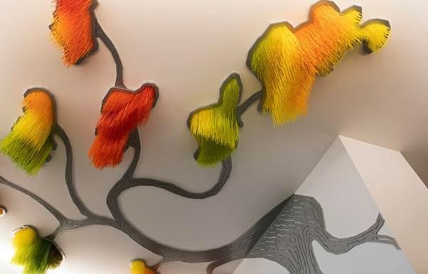 Những bông hoa được làm bằng nhựa nhân tạo nhiều màu sắc được ốp theo dạng thả từ trên thả xuống.