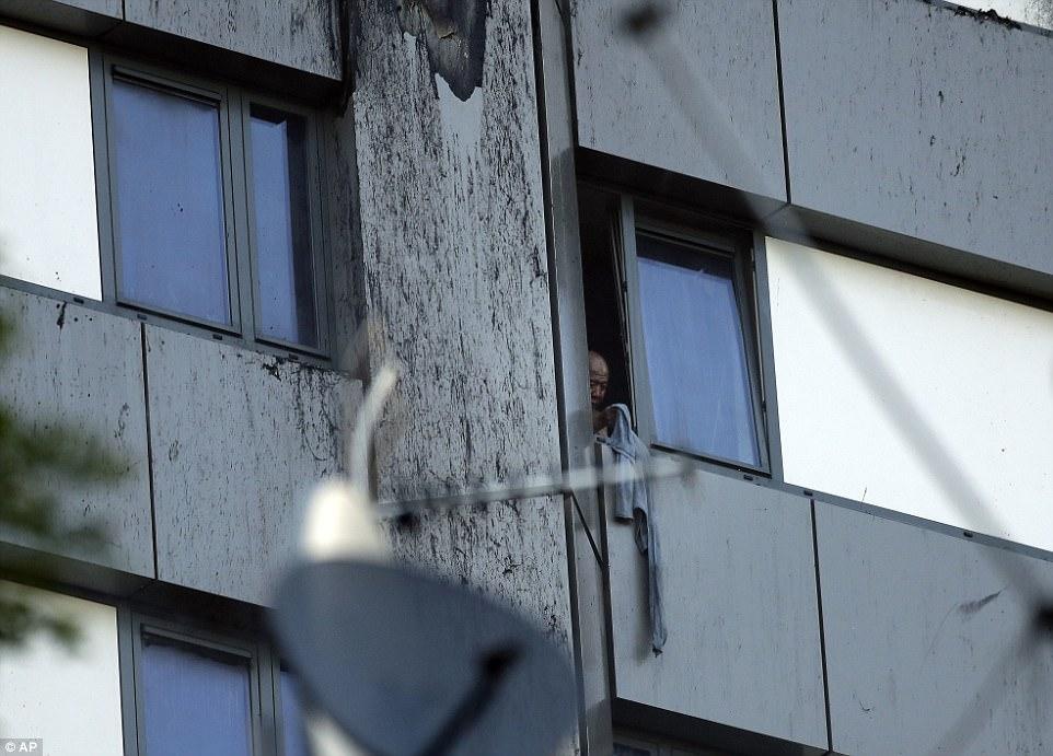 Ít nhất một người còn sống vẫn đang mắc kẹt trong tòa nhà. Lực lượng cứu hộ đang nỗ lực giải cứu người đàn ông ở tầng 11, mặt chưa bị lửa thiêu rụi của tòa nhà. Ảnh: AP
