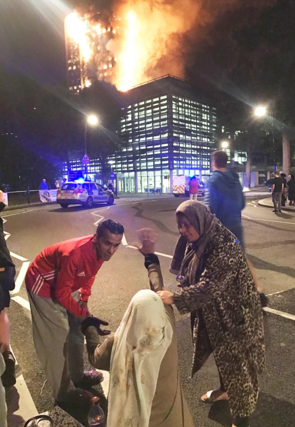 Một phụ nữ tuyệt vọng khi nhìn đám cháy bao phủ ngôi nhà, nơi thân nhân của bà vẫn đang mắc kẹt. Hiện tại, nhà chức trách Anh chưa thể xác định chính xác số nạn nhân của vụ hỏa hoạn kinh hoàng. Ảnh: Daily Mail