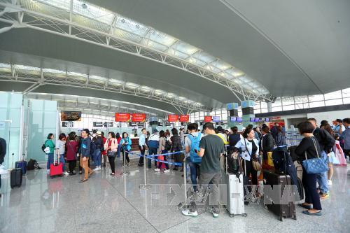 Hành khách làm thủ tục lên máy bay tại Cảng hàng không quốc tế Nội Bài. Ảnh: Huy Hùng/TTXVN