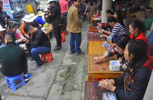 Sáng sớm, hàng chục gian hàng được bày bán giữa khuôn viên chợ huyện. Mỗi gian hàng rộng chưa đến 1m2 với một bàn, một ghế và một chủ.