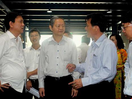 Bí thư Thành ủy TP.HCM Đinh La Thăng (bìa trái) cùng Phó Chủ tịch UBND TP Lê Văn Khoa (giữa) đang trao đổi với lãnh đạo Cảng hàng không Tân Sơn Nhất. Ảnh: HỒNG TRÂM