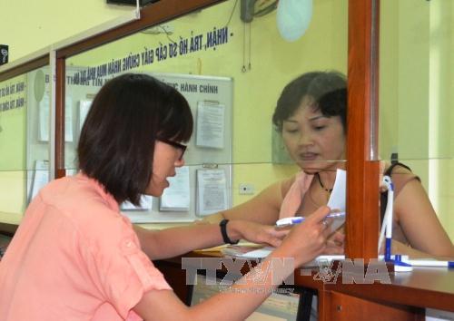 Hướng dẫn thủ tục cho người dân tại bộ phận một cửa Văn phòng Đăng ký đất đai Hà Nội. Ảnh: Đỗ Phương Anh/TTXVN