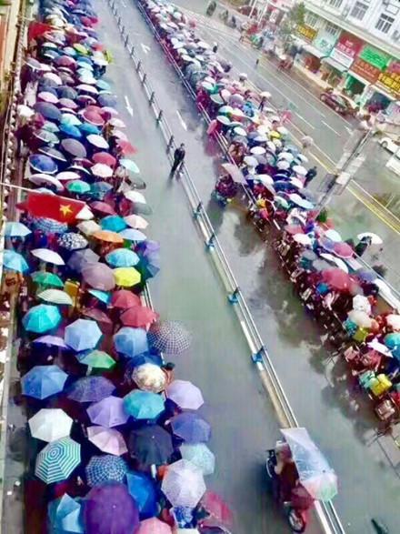 Dòng người xếp hàng dài dưới mưa đợi đến lượt xuất cảnh bên cửa khẩu Đông Hưng.