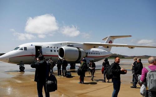 Hành khách chuẩn bị lên một máy bay của Air Koryo ở sân bay Bình Nhưỡng hôm 18/4 - Ảnh: Reuters.