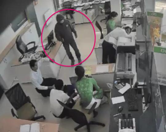 Tên cướp yêu cầu nhân viên gom tiền. Ảnh: Cắt từ camera an ninh