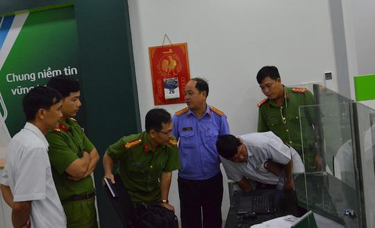 Khám nghiệm hiện trường vụ cướp tại ngân hàng Vietcombank chi nhánh Duyên Hải vào tối 26-4. Ảnh: Hồng Dương