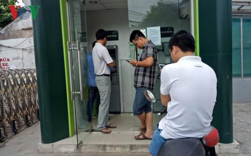 Người dân chờ đợi rút tiền từ ATM (có 2 cây nhưng 1 cây đã ngừng giao dịch vì cạn tiền)