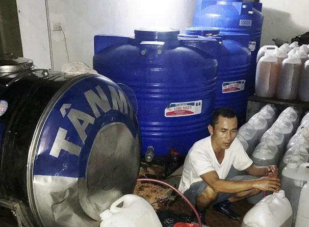 Đối tượng Nguyễn Quốc Tuấn bị bắt quả tang sang chiết đóng can số lượng lớn dầu ăn không rõ nguồn gốc xuất xứ.