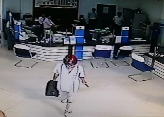 Kẻ cướp ung dung bước ra ngoài sau khi cướp trên 200 triệu đồng. Ảnh cắt ra từ camera an ninh