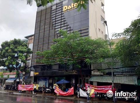 Khách hàng mua căn hộ tại dự án Đạt Gia Residence đội mưa, căng băng rôn trước trụ sở công ty Đạt Gia đòi quyền lợi.