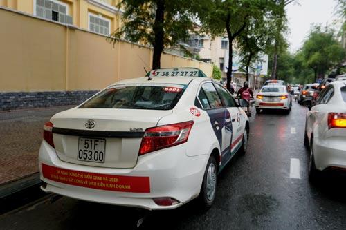 Chiều 9-10, nhiều taxi Vinasun tại TP HCM vẫn dán biểu ngữ phản đối Uber, Grab Ảnh: Gia Minh