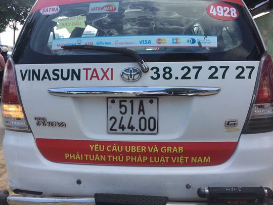 Khẩu hiệu phản đối Uber, Grab dán sau một taxi Vinasun lưu thông trên đường phố TP HCM sáng 8-10.