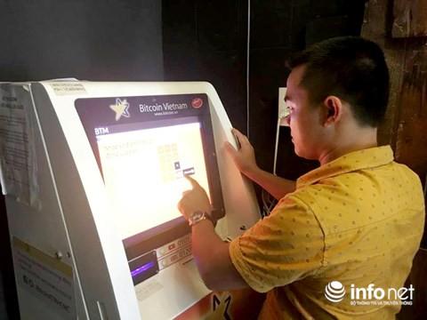 Một khách hàng đang giao dịch Bitcoin qua máy BTM đặt tại quán cà phê ở TP.HCM.