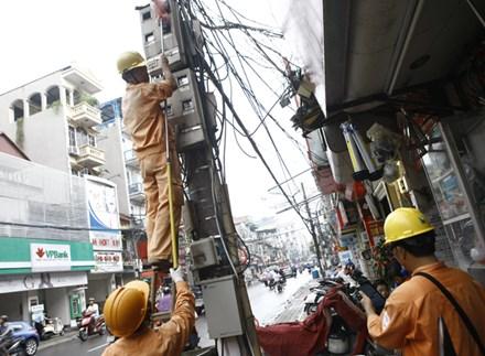 Nhân viên Cty Điện lực Hà Nội ghi chỉ số công tơ điện của các hộ dân trên phố Khâm Thiên - Hà Nội. Ảnh: Như Ý.
