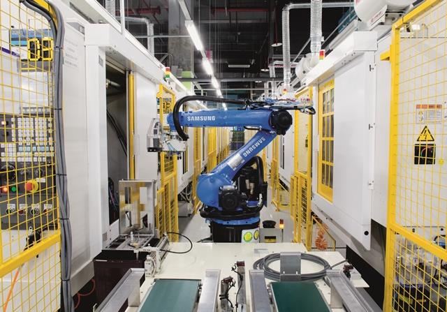 Đây là robot chuyên dụng, giúp chuyển máy vào trong máy cắt cơ khí bằng máy tính (CNC) thay cho công nhân. Trong nhà máy vẫn còn nhiều vị trí do con người đảm nhận nhưng qua quan sát, những chú robot như thế này nhanh hơn nhiều.