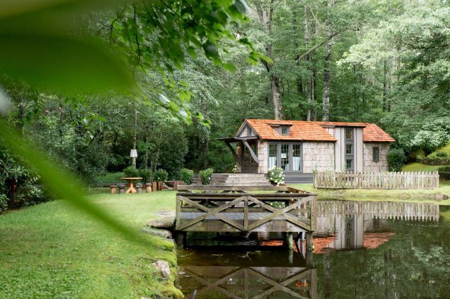 Ngôi nhà nhỏ tuyệt đẹp nằm nép mình giữa hồ nước và rừng cây. Lối vào nhà là một thảm cỏ xanh mướt chạy dài.