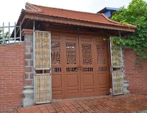 Cổng cũng được làm bằng gỗ lim, bên trên lợp ngói vẩy.