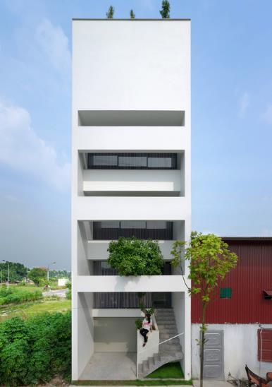 Toàn bộ ngôi nhà 5 tầng màu trắng rộng thoáng nhìn từ bên ngoài. Tầng 1 là khu vực để xe và kho chứa đồ, các tầng trên là không gian bố trí các khu vực chức năng của ngôi nhà.